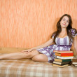 Girl with books on sofa — Stock Photo #3816200