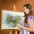 Girl with brushes near easel — Stock Photo #3816205