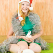 Girl in santa hat with abbits — Stock Photo