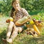 Girl sitting near harvested vegetables — Stock Photo