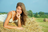 Young woman on hay bail — Stock Photo