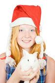 Girl in santa hat with rabbit — Stock Photo