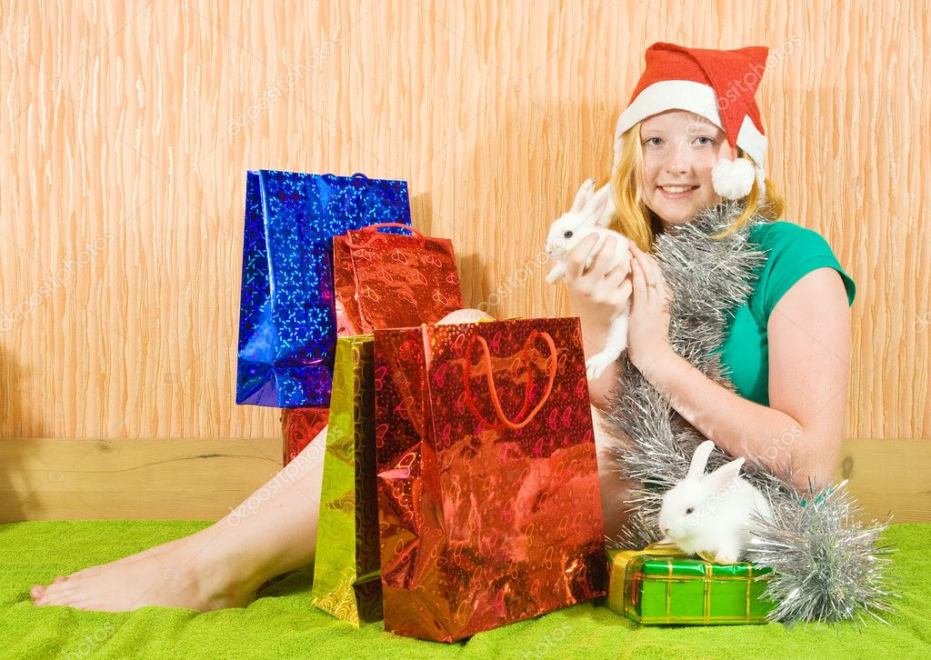 Teenager girl  with Christmas gifts and two pet rabbits  — Stock Photo #3814591