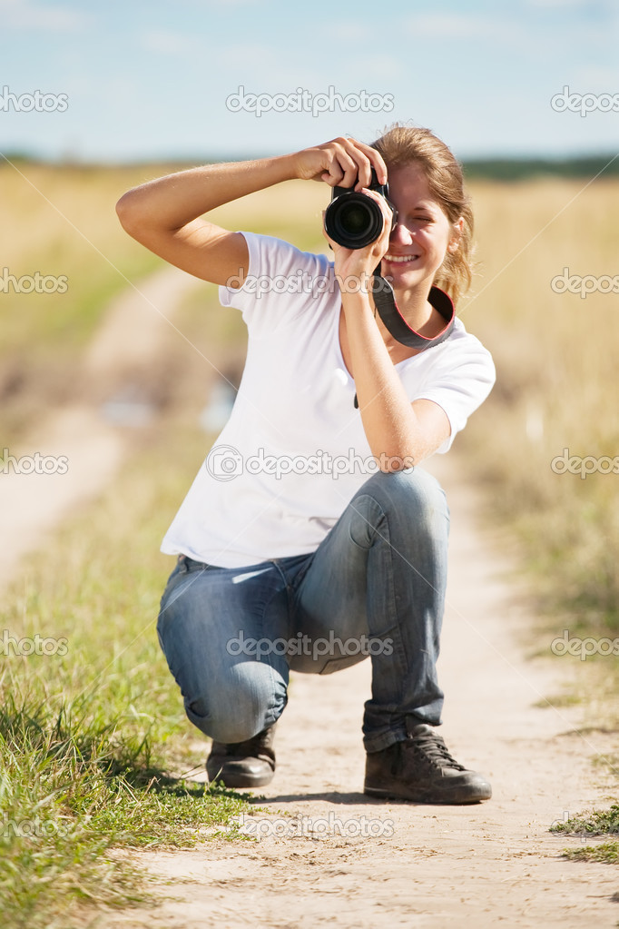 Young girl taking photo with camera against field  Stock Photo #3814818