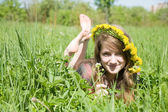 Girl in a chaplet lying from meadow — Stock Photo