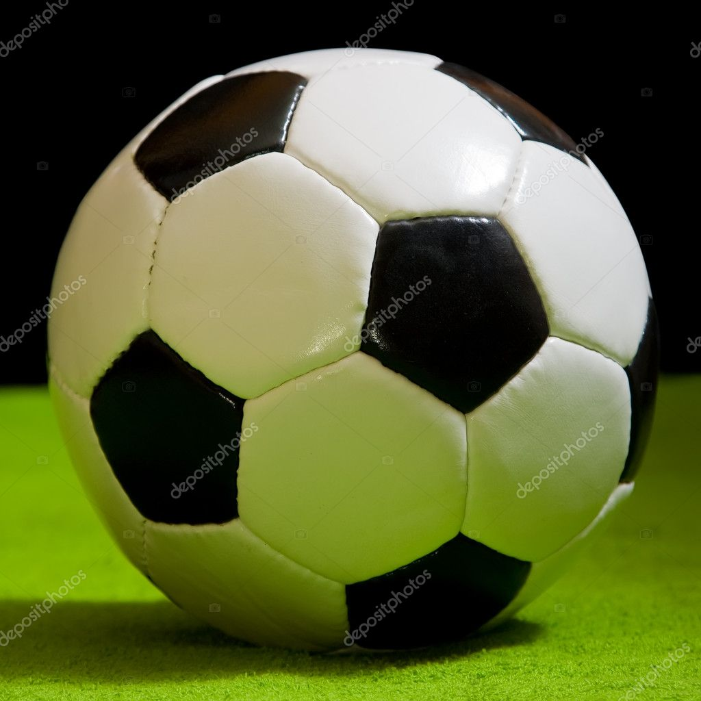 Classic football ball on green over black. football simbol — Stock Photo #3825476