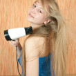 Blonde girl using hairdryer — Stock Photo