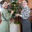Two women decorating Christmas tree — Stock Photo
