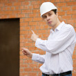 Royalty-Free Stock Photo: Builder pointing to door in brick wall