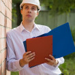 Builder in hard hat with documents — Stock Photo