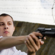 Man aiming a black gun - Stock Photo