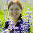 Woman in plant of violet wild lupine - Stock Photo