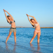 Girls doing yoga against sea — Stockfoto