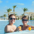 Girls relaxing in tropical pool with orange juice — Stock Photo