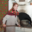 Woman puts a pot into russian stove — Stock Photo #3839213