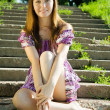 Girl in dress sitting on stair — Stock Photo #3839596