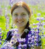 Woman in plant of violet wild lupine — Stock Photo