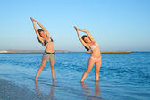 Girls doing yoga against sea — Stock Photo