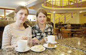 Beautiful girls relaxing at coffee-room with a cup of tea — Stock Photo
