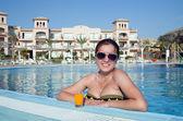 Dziewczyna w tropikalnym basenie z soku pomarańczowego — Zdjęcie stockowe