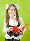 Schoolgirl reading red book — Stock Photo