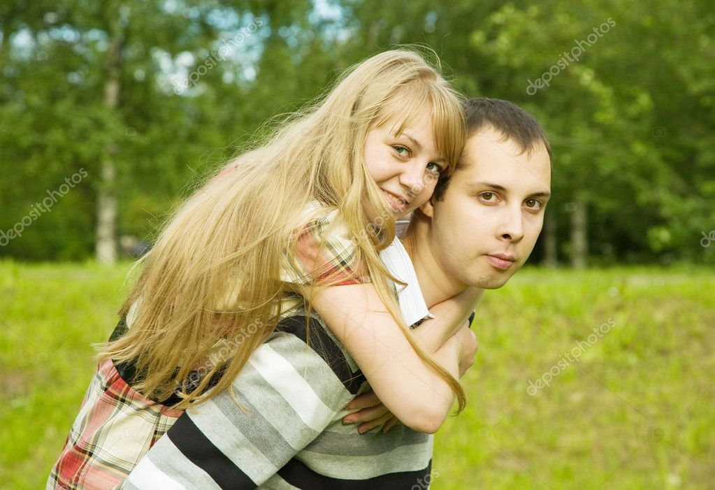Pretty girl embracing handsome boyfriend while both laughing and looking aside — Stock Photo #3833036