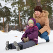 Foto Stock: Child sliding in snow with her mother