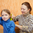 Stock Photo: Mother combs the hairs of daughter