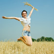 Jumping girl  with  wheat ear - Stock Photo