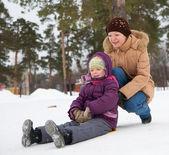 Criança deslizando na neve com sua mãe — Foto Stock