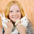 Stock Photo: Girl in tinsel with two pet rabbits