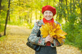 Woman with maple leaves in autumn park — Stock Photo