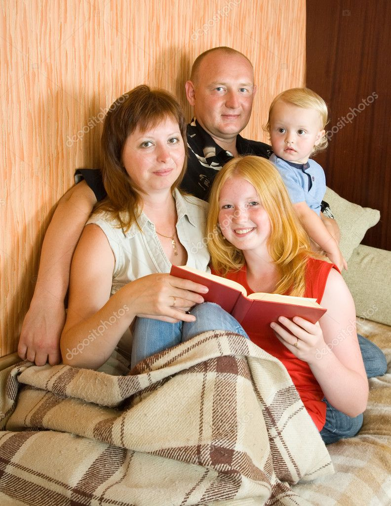Father, mother and children reading  book at home — Stock Photo #4098843