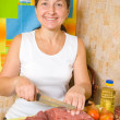 Mature woman is cooking beef — Stock Photo