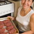 Woman putting stuffed beef  into oven - Zdjcie stockowe