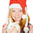 Girl in santa hat with rabbit — Stock Photo