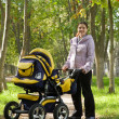 Mother walking with pram — Stock Photo