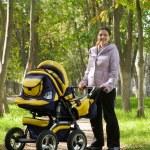 Mother walking with pram — Stock Photo