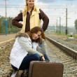 Tired women on rail station - Stock Photo