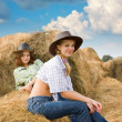 Farm girls restings on  hay — Stock Photo