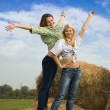 Two girls standing on hay — Stock Photo