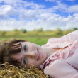 Girl resting on hay — Stock Photo