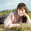 Girl on hay in summer — Stock Photo