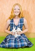 Teen girl with rabbits indoor — Stock Photo