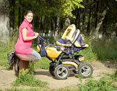 Woman with pram in park — Stock Photo