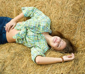 Girl on straw bale — Stock Photo