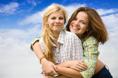 Pretty girl embracing girlfriend — Stock Photo
