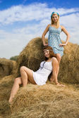 Country girls on hay in summer — Stock Photo