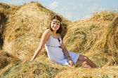Girl on hay at field — Stock Photo
