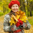 Portrait of senior woman  in autumn - Stock Photo